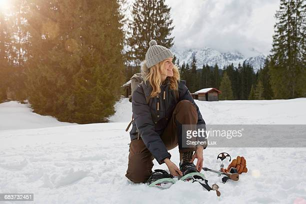 Mature woman putting on snow shoes in snowy landscape, Elmau, Bavaria, Germany