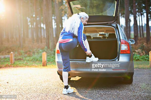 Mature woman putting on trainers on car boot