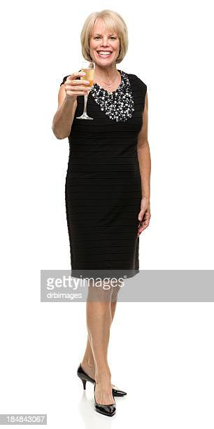 mature woman raises champagne glass toast - evening gown stock pictures, royalty-free photos & images