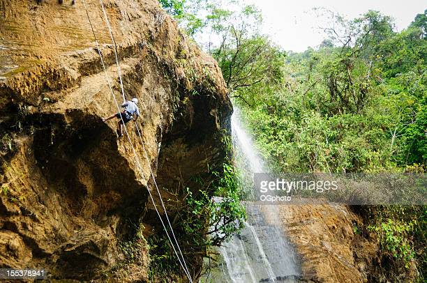 Mature woman rappeling next to a waterfall