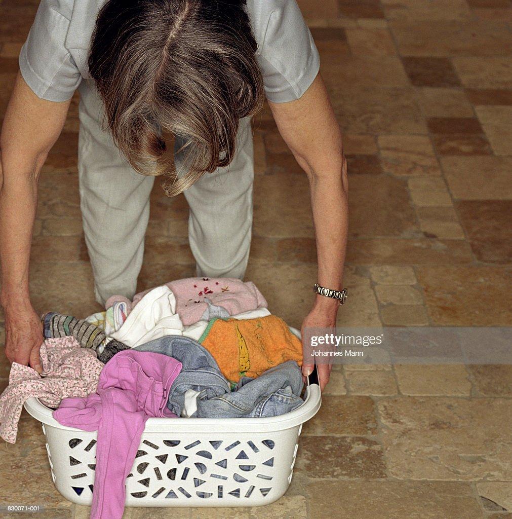 Mature woman reaching to pick up laundry basket : Stock Photo