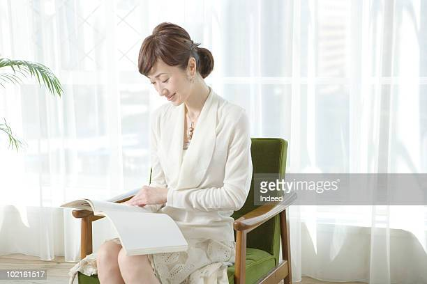 mature woman reading a book, in the living room - 中年の女性一人 ストックフォトと画像