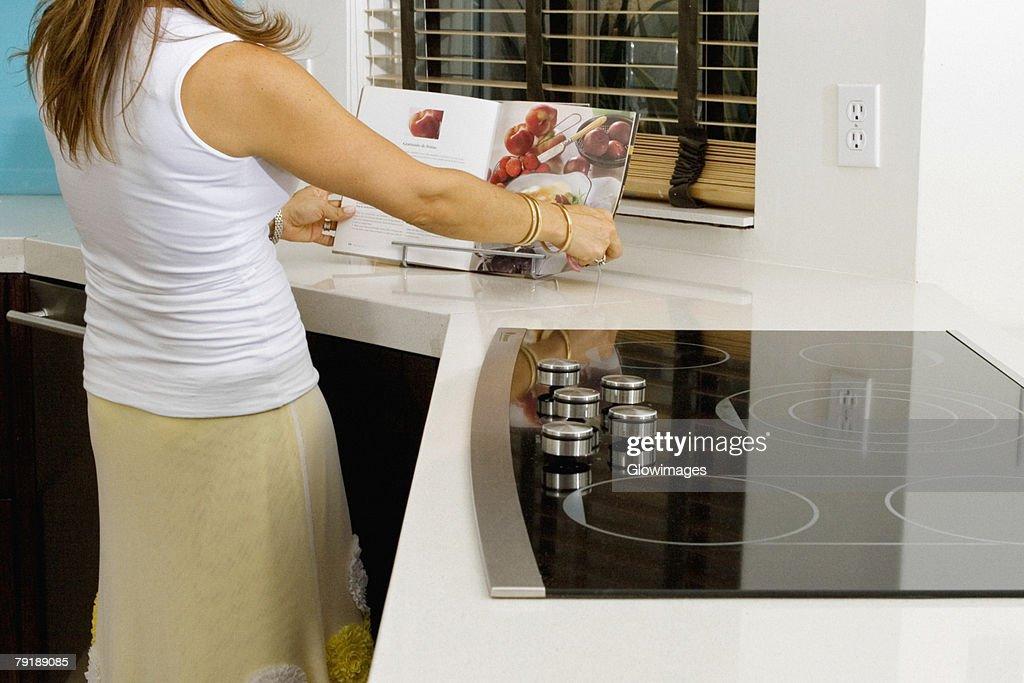 Mature woman reading a cookbook at a kitchen counter : Foto de stock
