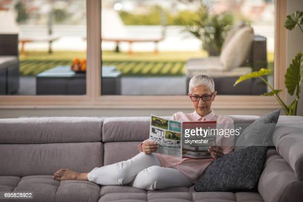 mature woman reading a magazine and enjoying a day at home. - magazine stock pictures, royalty-free photos & images