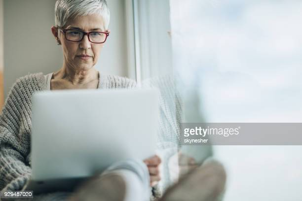 mature woman reading an e-mail on laptop by the window. - reading glasses stock pictures, royalty-free photos & images