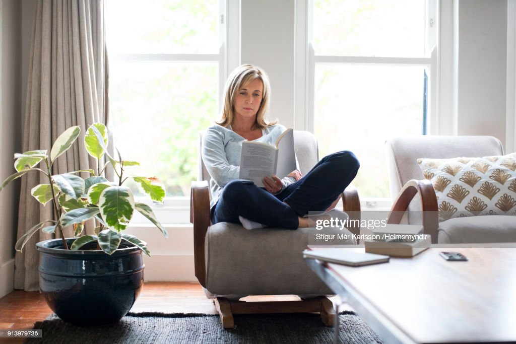 Mature woman reading book on chair at home : Stock Photo