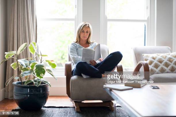 mature woman reading book on chair at home - legge foto e immagini stock