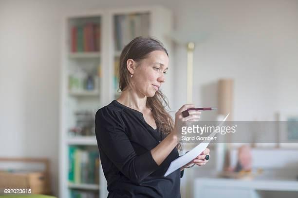 mature woman reading document - sigrid gombert stock-fotos und bilder