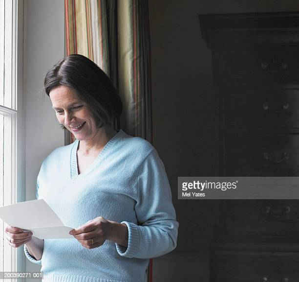 Mature woman reading letter by window, smiling