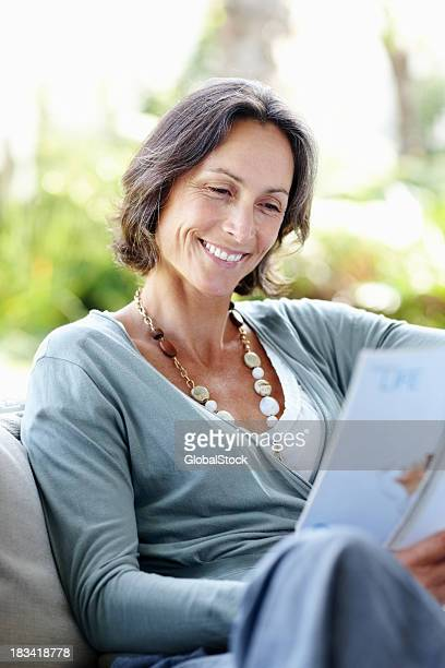 Mature woman reading magazine at home on the sofa