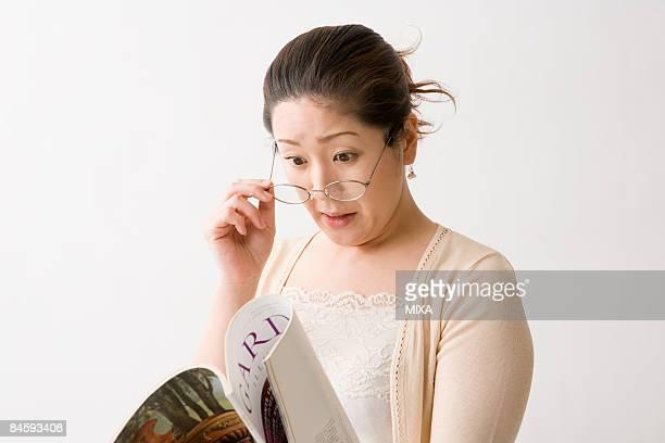 Mature woman reading magazine