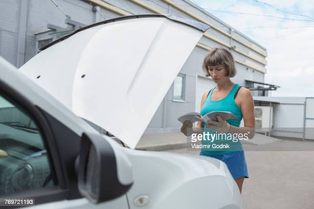 mature woman reading manual while standing by breakdown car - instruction manual stock photos and pictures