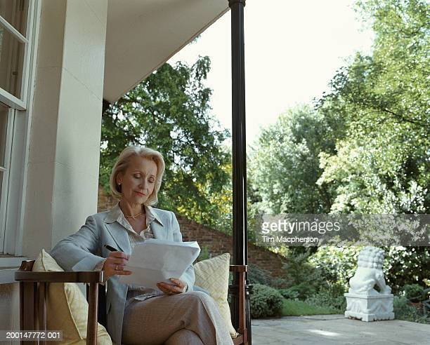 Mature woman reading paperwork by patio window