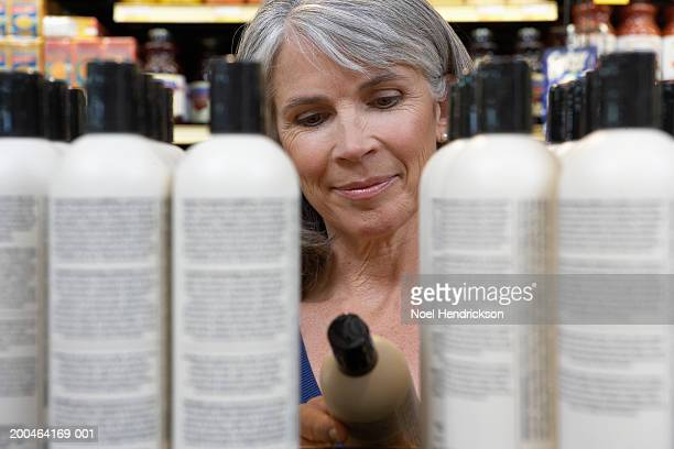 Mature woman reading shampoo label in store, close-up