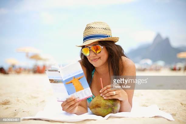 Mature woman reading tourist guide, Ipanema beach, Rio De Janeiro, Brazil