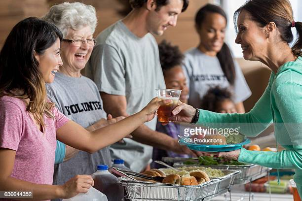 Mature woman receives healthy meal in soup kitchen