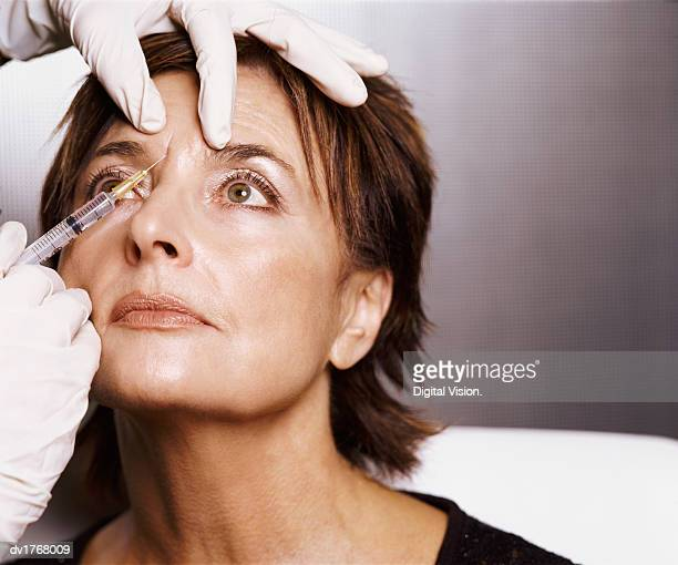 mature woman receiving an injection to her forehead - botox stock pictures, royalty-free photos & images
