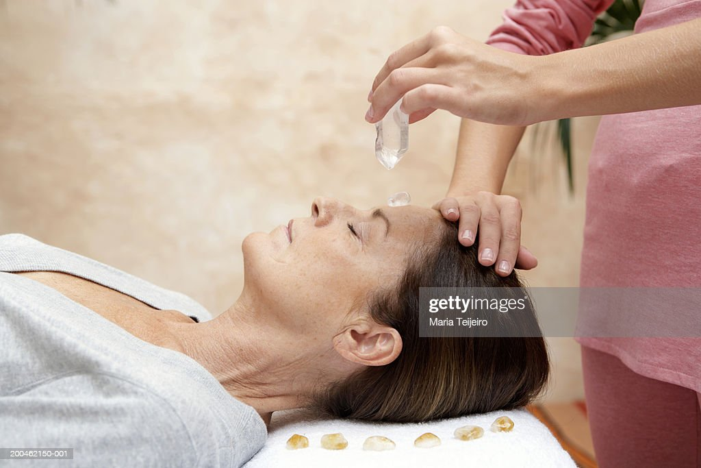 Mature woman receiving crystal healing treatment, eyes closed : Stock Photo