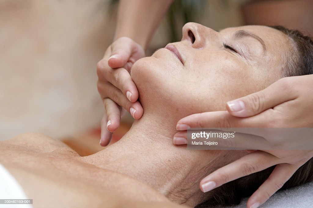 Mature woman receiving massage, eyes closed, close-up : Stock Photo