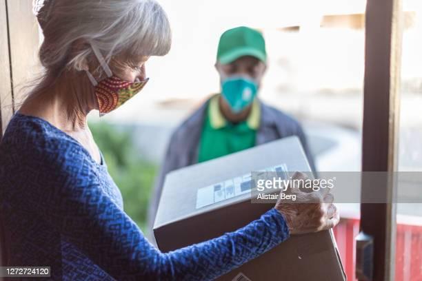mature woman receiving package from courier - receber - fotografias e filmes do acervo