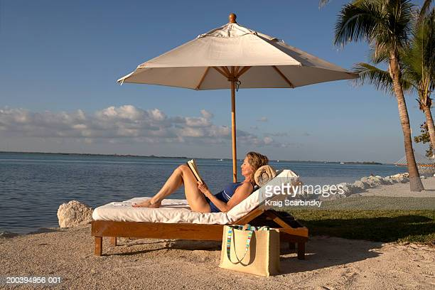 mature woman reclining on sun lounger holding book, eyes closed - parasol de plage photos et images de collection