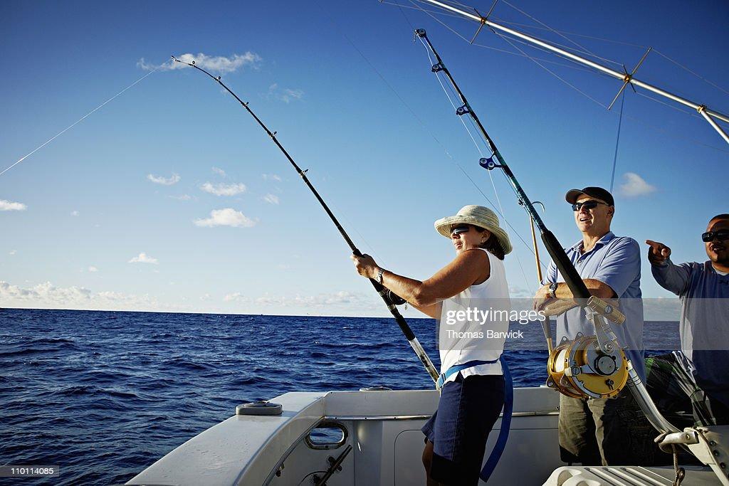 Mature woman reeling in fish : Stock Photo