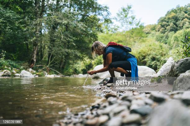 mature woman refreshes herself in stream in the morning - freshwater stock pictures, royalty-free photos & images