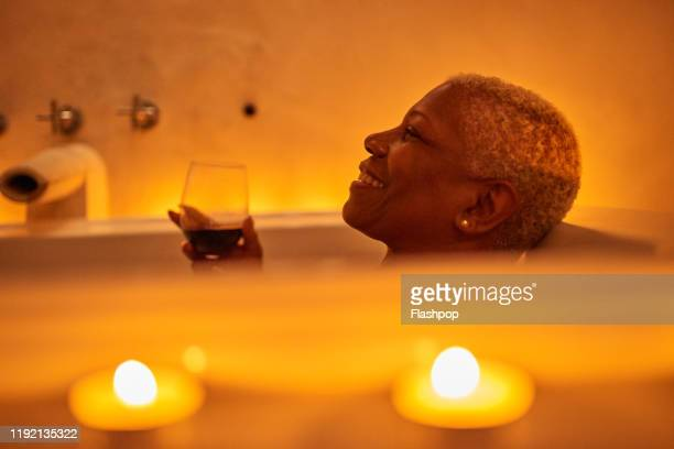 mature woman relaxes in bath - candlelight stock pictures, royalty-free photos & images