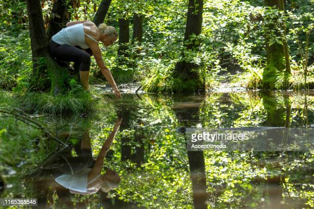 mature woman relaxes in forest by pond - reflection pool stock pictures, royalty-free photos & images