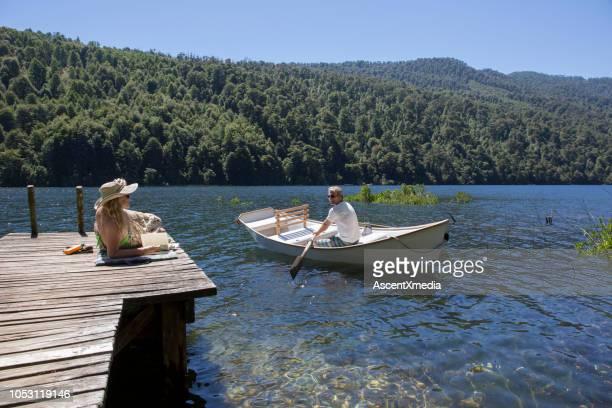 mujer madura se relaja en el muelle mientras el barco de las filas de hombre en el lago - pucon fotografías e imágenes de stock