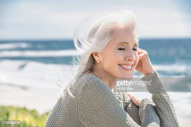 Mature woman relaxing at beach with eyes closed