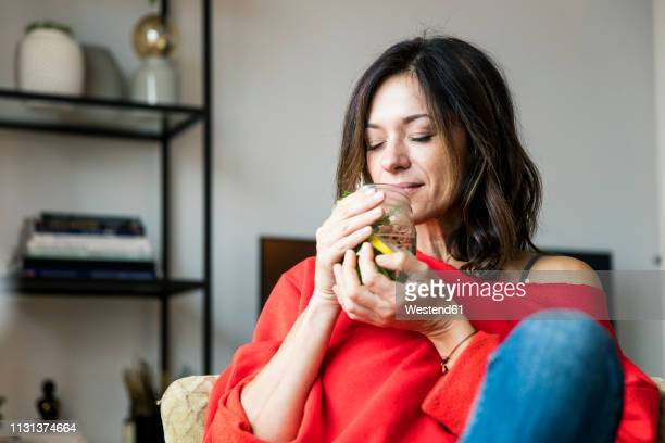 mature woman relaxing at home, drinking lemon water - infused water stock pictures, royalty-free photos & images