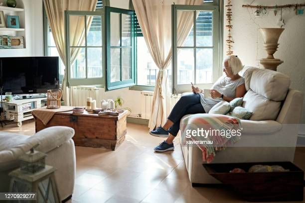 mature woman relaxing at home with smart phone and coffee - two seater sofa stock pictures, royalty-free photos & images