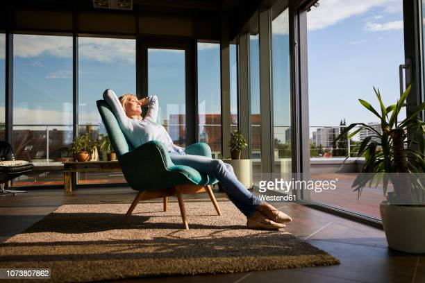 mature woman relaxing in armchair in sunlight at home - comfortabel stockfoto's en -beelden