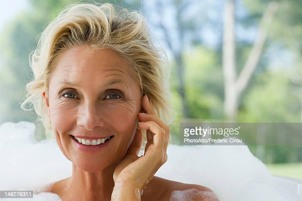 Mature woman relaxing in bubble bath, portrait