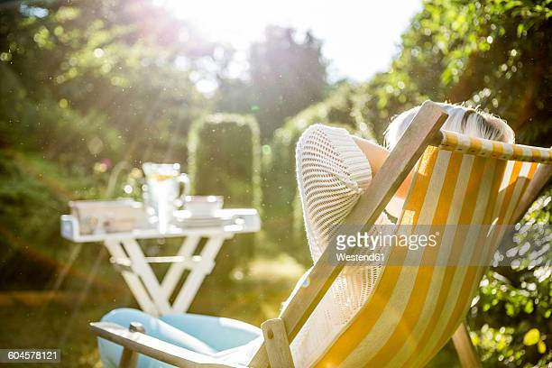 Mature woman relaxing in deckchair in garden