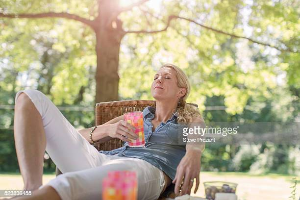mature woman relaxing in garden with drink - one mature woman only stock pictures, royalty-free photos & images