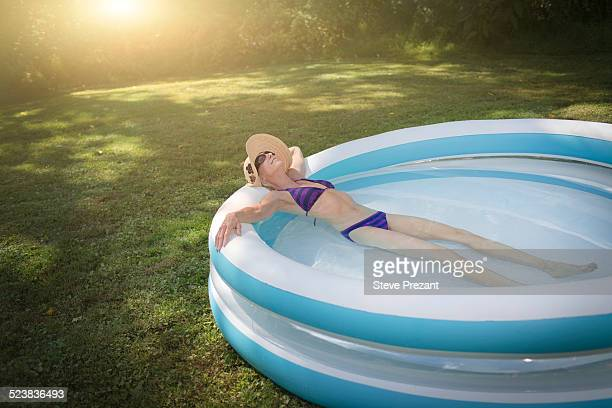 Mature woman relaxing in paddling pool