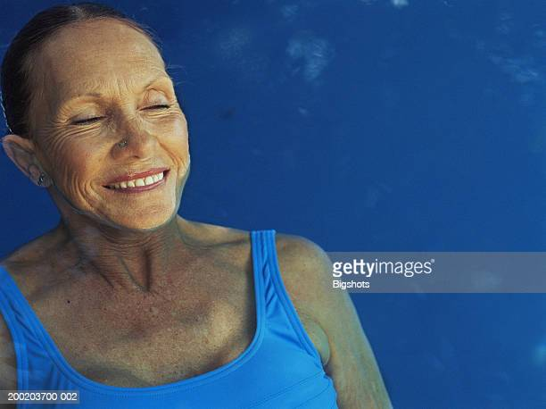 mature woman relaxing in pool, smiling, eyes closed, close-up - alte frau badeanzug stock-fotos und bilder
