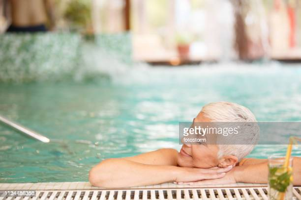 mature woman relaxing in swimming pool - health farm stock pictures, royalty-free photos & images