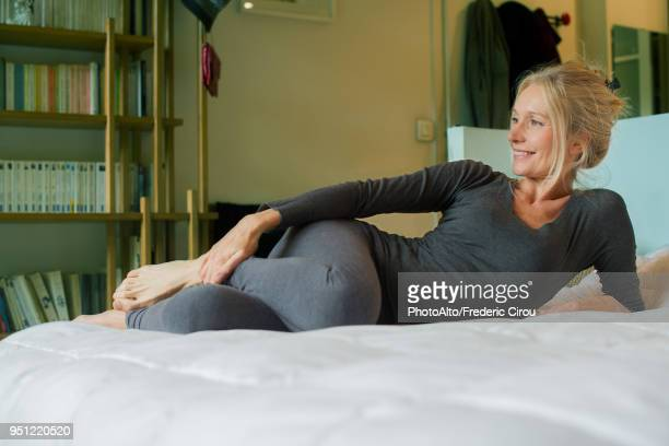 mature woman relaxing on bed - donne bionde scalze foto e immagini stock