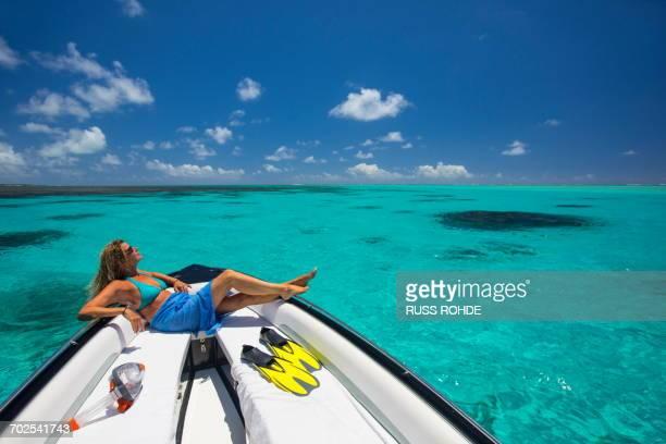 mature woman relaxing on boat, ile aux cerfs, mauritius - isole mauritius foto e immagini stock