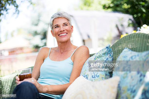 Mature woman relaxing on garden seat