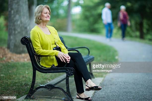Femme d'âge mûr se détendre sur un banc.