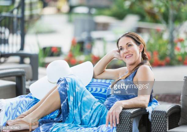mature woman relaxing on pool deck - sundress stock pictures, royalty-free photos & images
