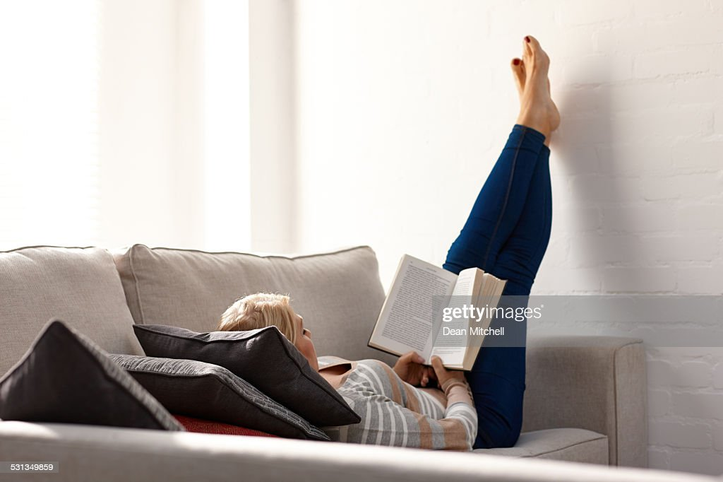 Mature Woman Relaxing On Sofa Reading A Novel : Stock Photo
