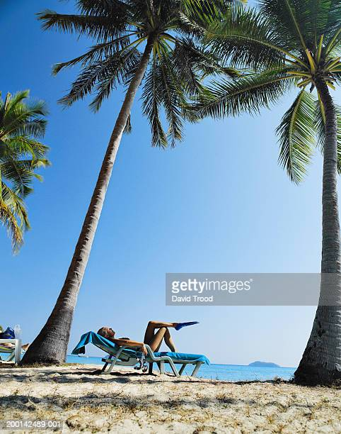 Mature woman relaxing on sunlounger under palm trees
