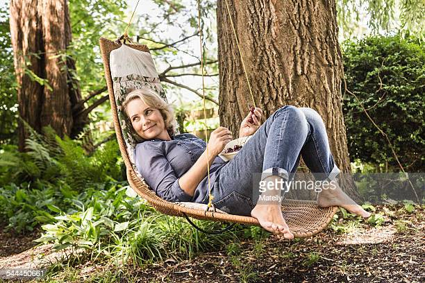 Mature woman relaxing with bowl of cherries on hammock