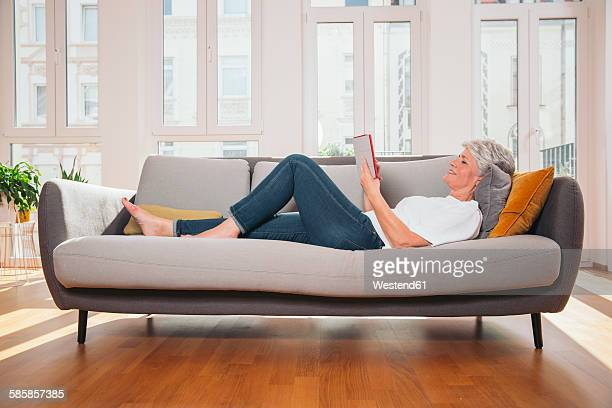 Mature woman relaxing with digital tablet on a couch at living room