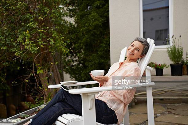 Mature woman relaxing with tea and digital tablet